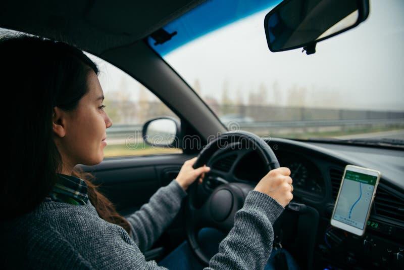 Mulher que conduz o carro pela estrada no tempo nevoento foto de stock