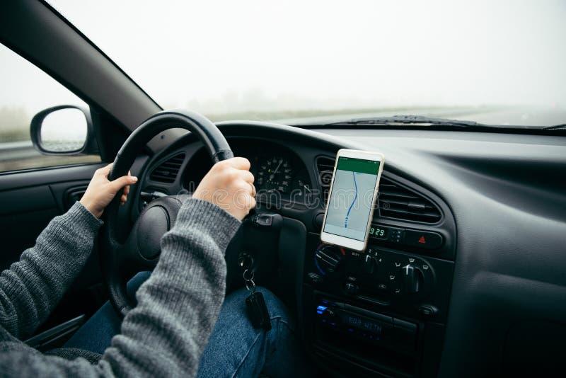 Mulher que conduz o carro pela estrada no tempo nevoento imagem de stock