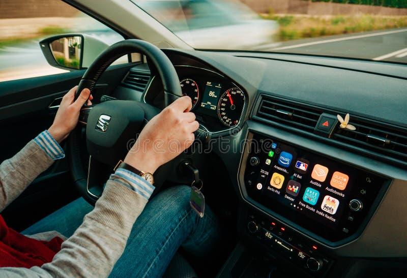 Mulher que conduz o carro rápido com o carro de Apple no painel foto de stock royalty free