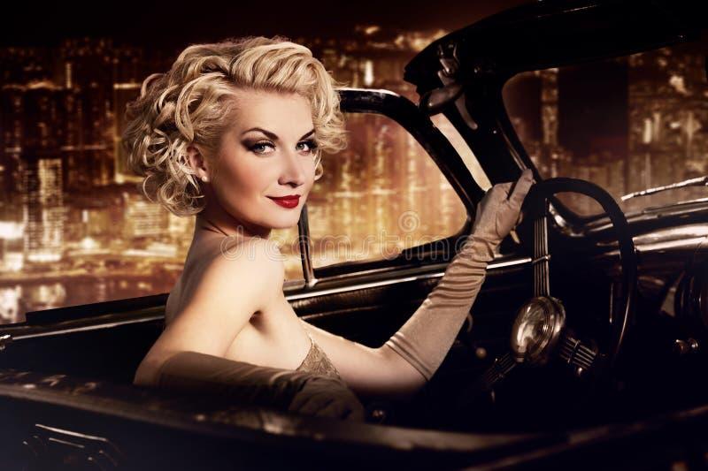 Mulher que conduz o convertible retro fotos de stock