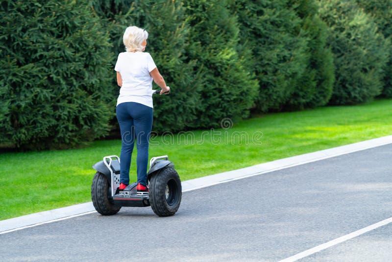Mulher que conduz o transportador pessoal ao longo da rua imagens de stock