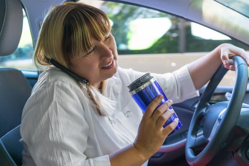A mulher que conduz um carro com o seu entrega ocupado fotografia de stock royalty free