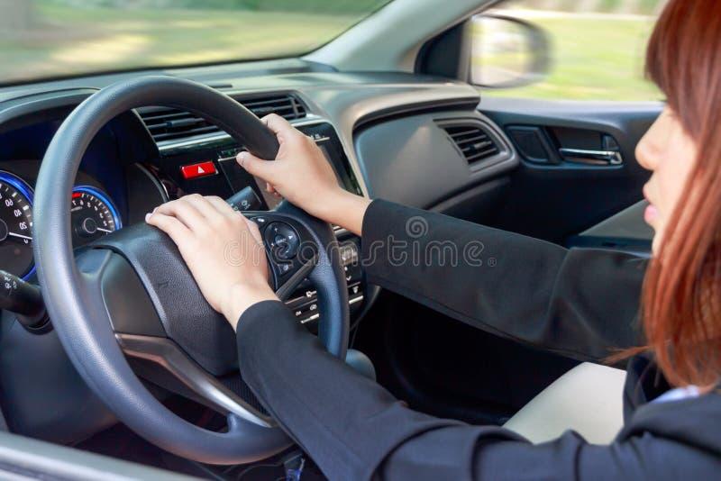 Mulher que conduz um carro e que pressiona no botão de chifre - transporte imagem de stock