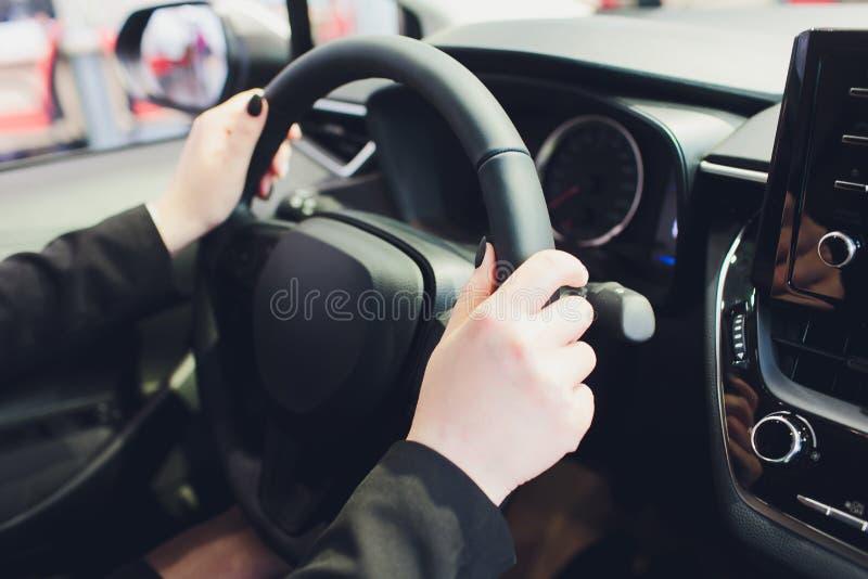 Mulher que conduz um carro, m?os no close-up do volante fotografia de stock