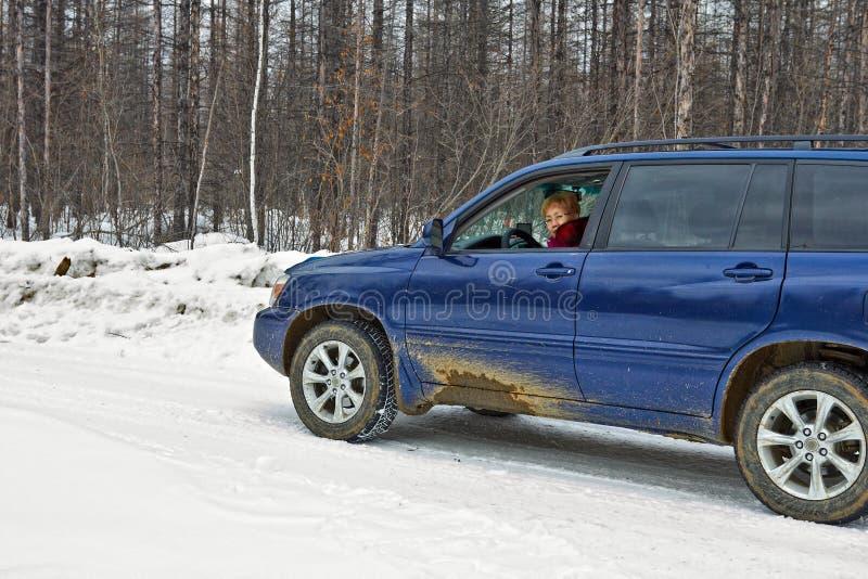 A mulher que conduz um carro monta ao longo da estrada do inverno imagem de stock royalty free