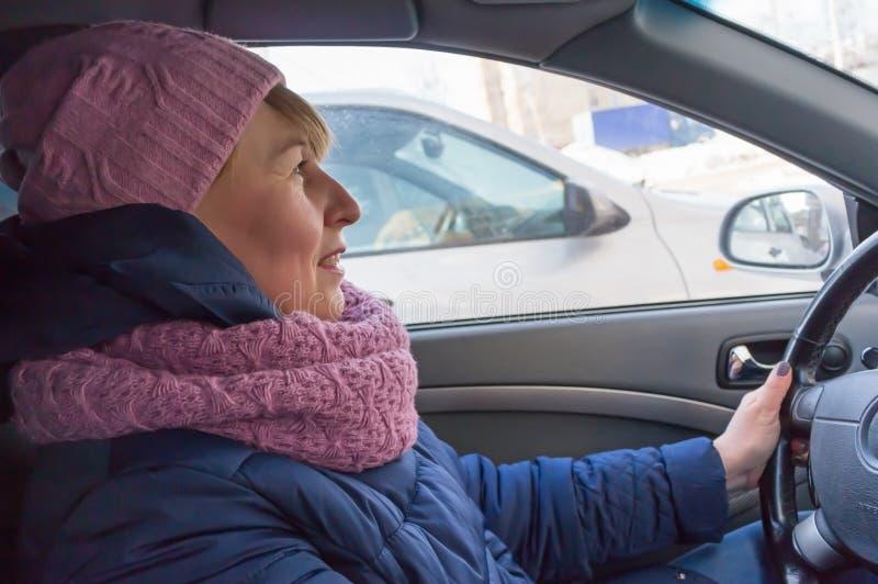 Mulher que conduz um carro no inverno fotos de stock
