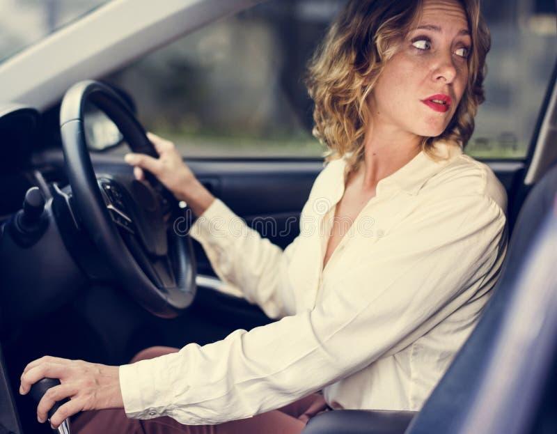 Mulher que conduz um carro no reverso fotografia de stock royalty free