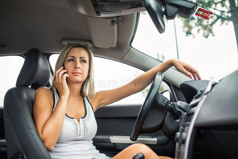 Mulher que conduz um motorista fêmea automobilístico em uma roda fotografia de stock