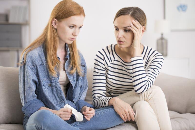 Mulher que consola a irmã deprimida triste imagem de stock