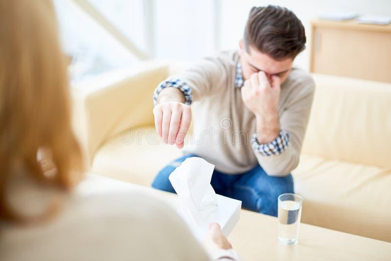 Mulher que consola o homem durante a psicoterapia imagem de stock royalty free