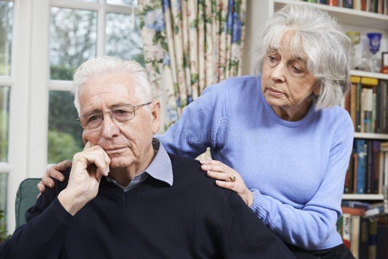 Mulher que consola o homem superior com depressão imagem de stock royalty free