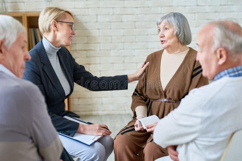 Mulher que consola pacientes superiores na reunião foto de stock