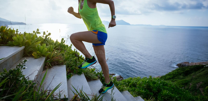 Mulher que corre acima em escadas da montanha do beira-mar fotografia de stock royalty free