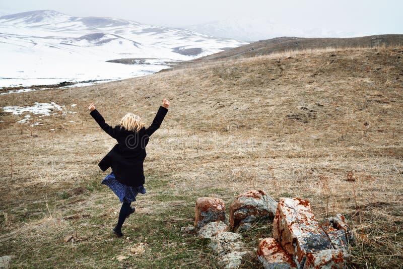 Mulher que corre afastado na paisagem da neve foto de stock