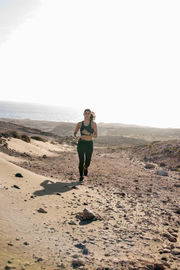 Mulher que corre através de uma duna de areia no deserto imagem de stock
