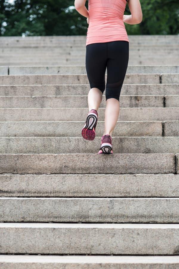 A mulher que corre em etapas no Central Park de New York que veste o esporte veste-se em horas de verão imagens de stock