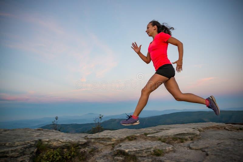 Mulher que corre em rochas Corta-mato fêmea que corre nas montanhas fotografia de stock