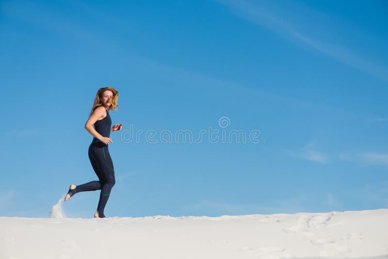 Mulher que corre na areia no desgaste do esporte imagem de stock
