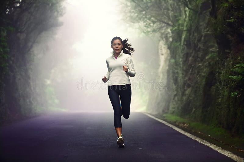Mulher que corre na estrada imagens de stock