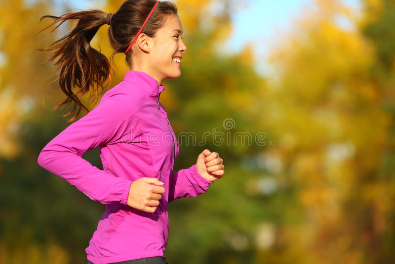 Mulher que corre na floresta da queda do outono imagens de stock