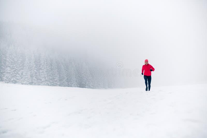 Mulher que corre na neve em montanhas do inverno fotos de stock