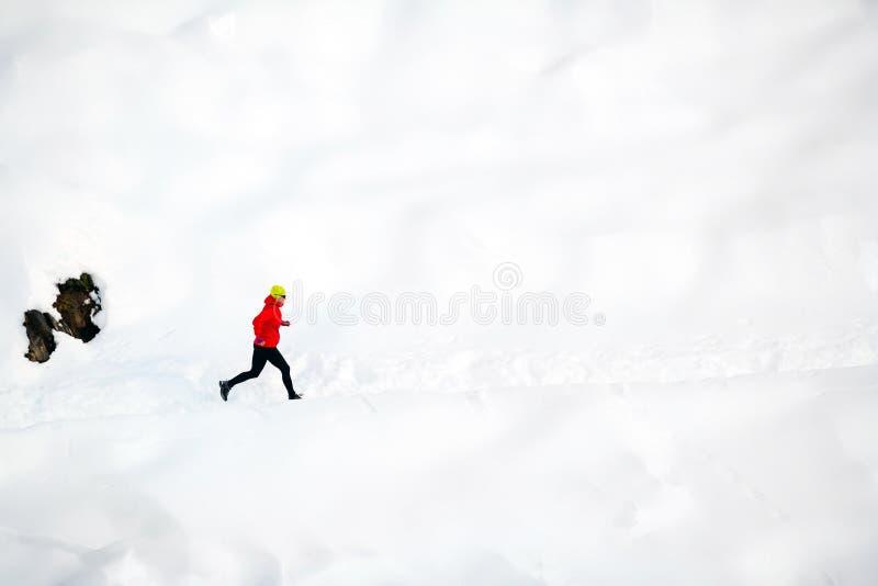 Mulher que corre na neve nas montanhas fotos de stock