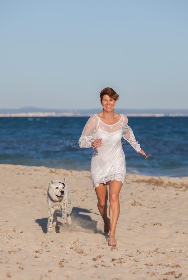Mulher que corre na praia com cão de estimação foto de stock royalty free