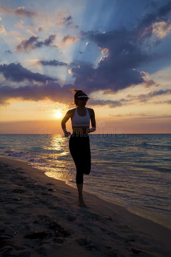 Mulher que corre na praia durante o por do sol imagens de stock royalty free