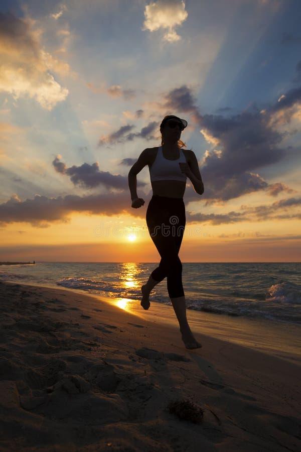 Mulher que corre na praia durante um por do sol bonito imagem de stock