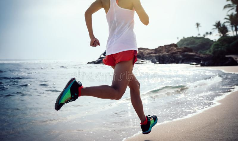 Mulher que corre na praia tropical imagens de stock