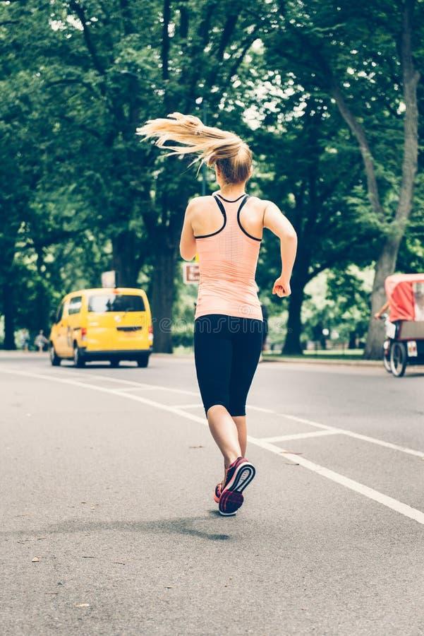 Mulher que corre no Central Park de New York City na manhã imagens de stock