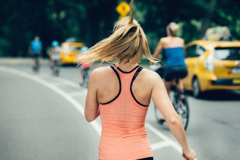 Mulher que corre no Central Park de New York City na manhã fotos de stock royalty free
