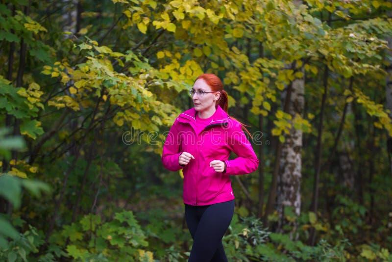 Mulher que corre no parque da queda do outono Fêmea na formação cor-de-rosa do revestimento e dos vidros exterior Imagem saudável imagens de stock