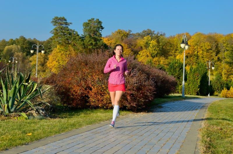 Mulher que corre no parque do outono, corredor bonito da menina que movimenta-se fora imagem de stock royalty free