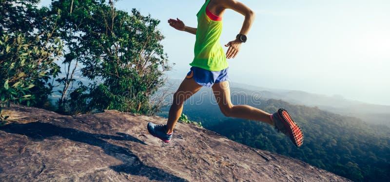 Mulher que corre no pico de montanha fotografia de stock