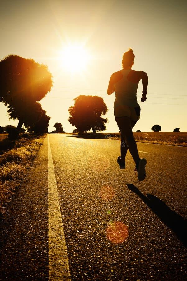 Mulher que corre no por do sol imagens de stock royalty free