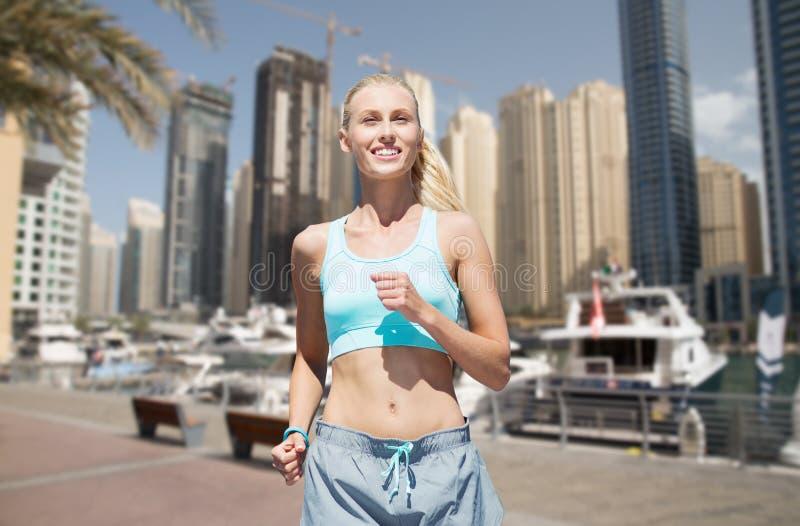 Mulher que corre ou que movimenta-se sobre a rua da cidade de Dubai foto de stock