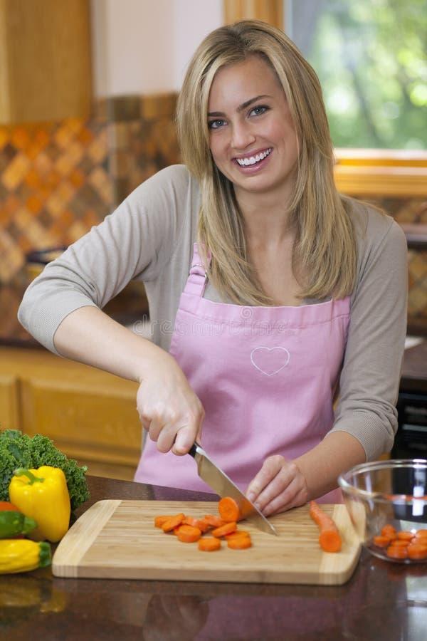 Mulher que corta o produto na cozinha foto de stock royalty free