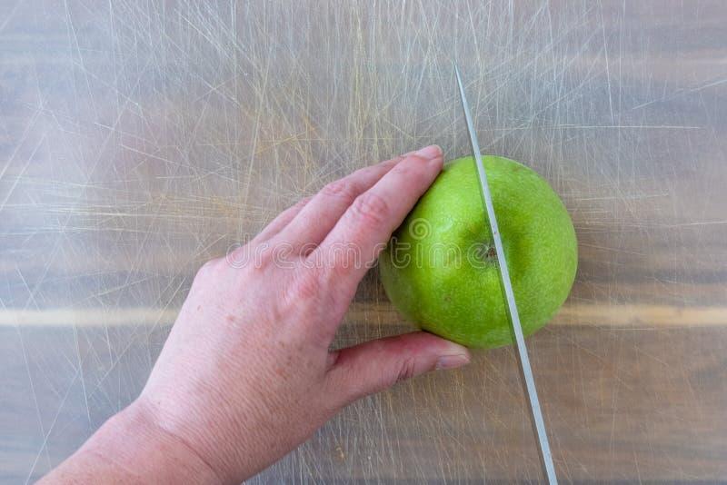 Mulher que corta uma maçã verde de Smith de avó em uma folha de corte plástica bem-usada sobre uma placa de corte de madeira, as  fotos de stock