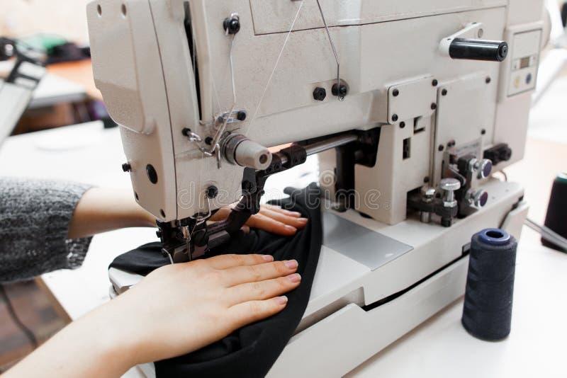 Mulher que costura a tela escura na máquina de costura fotografia de stock royalty free