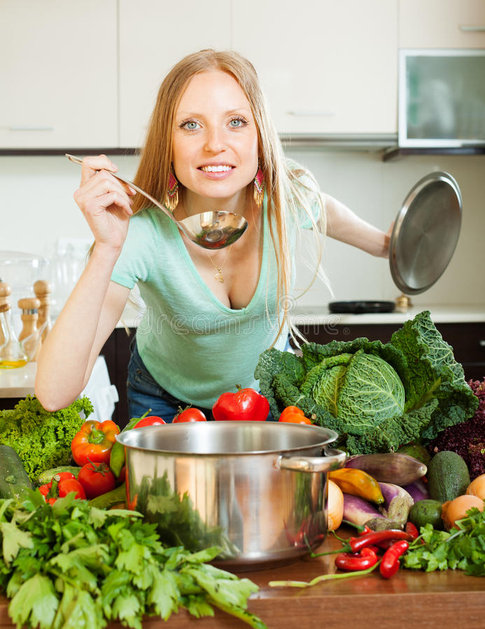 Mulher que cozinha com a concha na casa imagens de stock royalty free