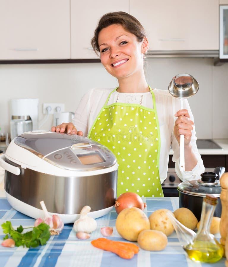 Mulher que cozinha com multicooker fotografia de stock royalty free