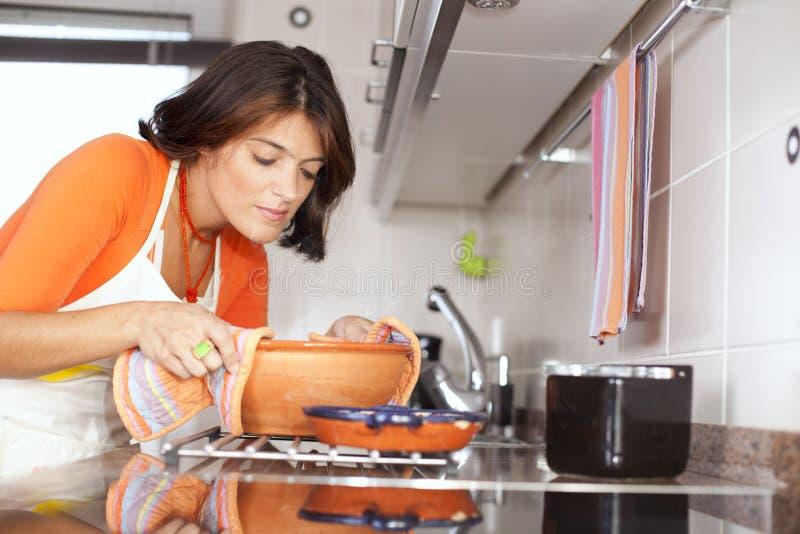 Mulher que cozinha em sua cozinha fotos de stock