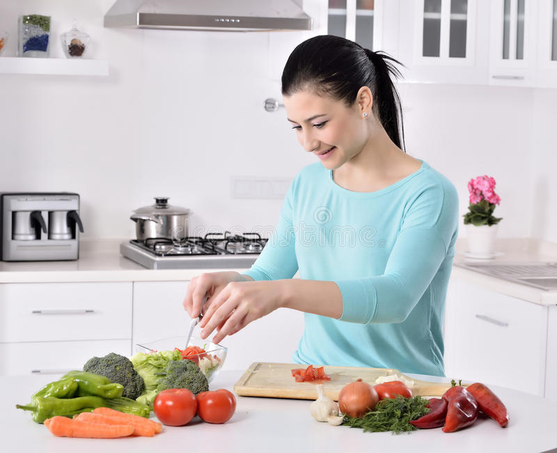 Mulher que cozinha na cozinha nova que faz o alimento saudável com vegetais imagens de stock royalty free