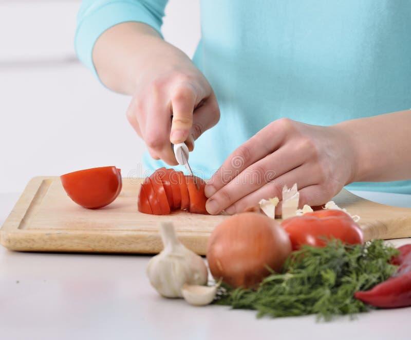 Mulher que cozinha na cozinha nova que faz o alimento saudável com vegetais fotos de stock royalty free