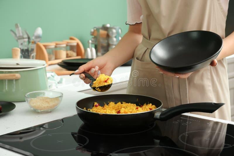 Mulher que cozinha o arroz no fogão na cozinha imagens de stock