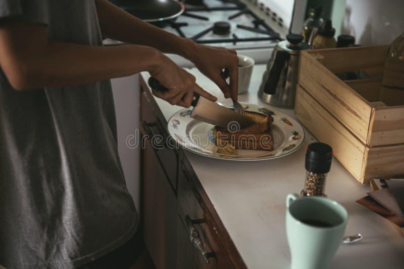 Mulher que cozinha o café da manhã na manhã imagens de stock