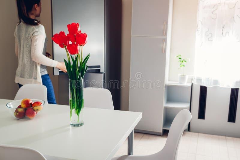 Mulher que cozinha o jantar na cozinha A moça abre o refrigerador para obter algum alimento Projeto moderno da cozinha foto de stock royalty free