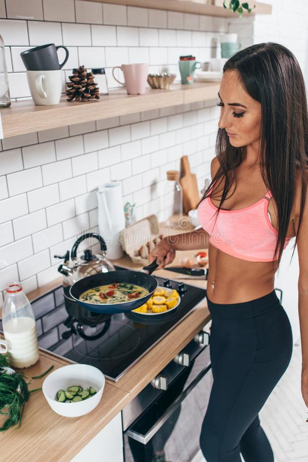 Mulher que cozinha o omlet que faz a posi??o saud?vel do alimento na cozinha em casa fotografia de stock