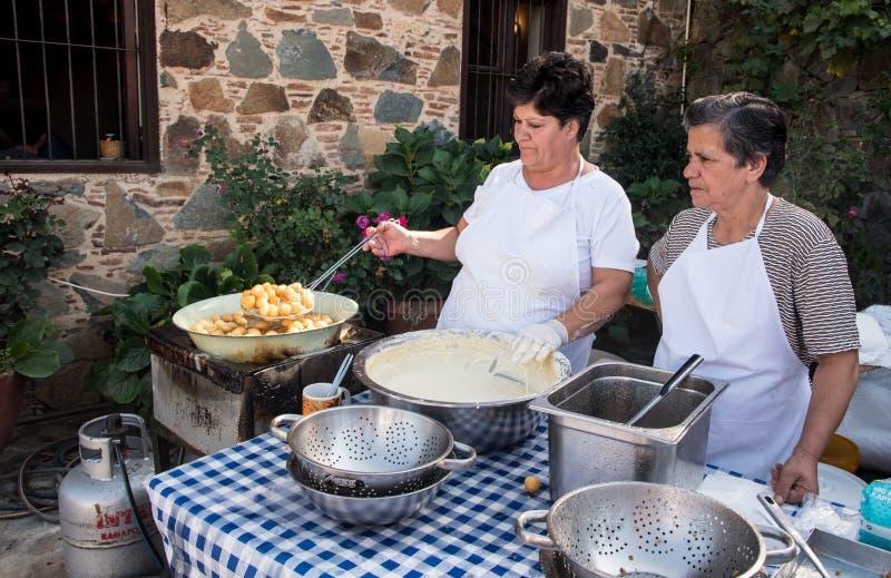 Mulher que cozinha a pastelaria deliciosa dos loukoumades foto de stock